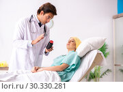 Купить «Young handsome doctor visiting female oncology patient», фото № 30330281, снято 3 октября 2018 г. (c) Elnur / Фотобанк Лори