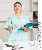 Купить «Girl doctor in medical coat holding clipboard with medical records», фото № 30347373, снято 1 мая 2018 г. (c) Яков Филимонов / Фотобанк Лори