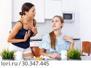 Купить «Upset young women friends quarrelling and drinking tea at home», фото № 30347445, снято 29 августа 2018 г. (c) Яков Филимонов / Фотобанк Лори
