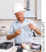 Купить «Man in hardhat engaged in renovation work», фото № 30356477, снято 19 июня 2018 г. (c) Яков Филимонов / Фотобанк Лори