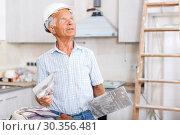 Купить «Foreman with plastering tools looking at repairable room», фото № 30356481, снято 19 июня 2018 г. (c) Яков Филимонов / Фотобанк Лори