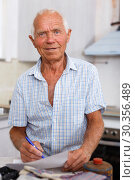 Купить «Enthusiastic man making list of repair works», фото № 30356489, снято 19 июня 2018 г. (c) Яков Филимонов / Фотобанк Лори