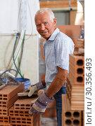 Купить «Man inspecting brick for installing wall», фото № 30356493, снято 19 июня 2018 г. (c) Яков Филимонов / Фотобанк Лори