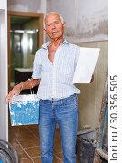 Купить «Senior man puttying walls», фото № 30356505, снято 19 июня 2018 г. (c) Яков Филимонов / Фотобанк Лори