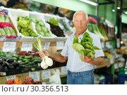 Купить «Elderly man looking for fresh vegetables», фото № 30356513, снято 16 июня 2018 г. (c) Яков Филимонов / Фотобанк Лори