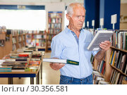 Купить «Portrait of intelligent older man choosing necessary books on shelves in library», фото № 30356581, снято 11 июня 2018 г. (c) Яков Филимонов / Фотобанк Лори