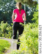 Купить «Adult female in pink T-shirt is jogging back», фото № 30356621, снято 10 июня 2017 г. (c) Яков Филимонов / Фотобанк Лори
