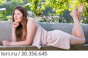 Купить «Cheerful woman is posing on bench in her free time», фото № 30356645, снято 10 июня 2017 г. (c) Яков Филимонов / Фотобанк Лори
