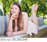 Купить «Cheerful elegant girl is lying on bench in her free time», фото № 30356649, снято 10 июня 2017 г. (c) Яков Филимонов / Фотобанк Лори