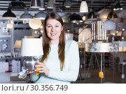 Купить «Smiling woman customer choosing torchere in store», фото № 30356749, снято 29 января 2018 г. (c) Яков Филимонов / Фотобанк Лори