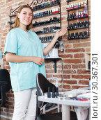 Купить «Smiling woman manicurist showing shelves with polish», фото № 30367301, снято 30 мая 2018 г. (c) Яков Филимонов / Фотобанк Лори