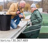 Купить «Owner of fish farm with worker checking sturgeons», фото № 30367489, снято 4 февраля 2018 г. (c) Яков Филимонов / Фотобанк Лори