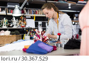 Woman sew up textile material at workplace at sewing workshop. Стоковое фото, фотограф Яков Филимонов / Фотобанк Лори