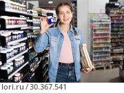 Купить «Girl shopping color in glass jar in art store», фото № 30367541, снято 12 апреля 2017 г. (c) Яков Филимонов / Фотобанк Лори