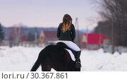 Купить «Winter time. A woman with red lipstick riding a horse in a village», видеоролик № 30367861, снято 23 июля 2019 г. (c) Константин Шишкин / Фотобанк Лори