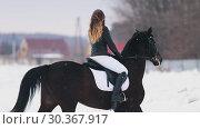 Купить «A young woman with long hair riding a horse in a village in winter time», видеоролик № 30367917, снято 16 июля 2019 г. (c) Константин Шишкин / Фотобанк Лори