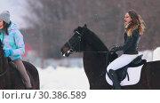 Купить «Winter time. Three women on horseback standing on snowy field in a village», видеоролик № 30386589, снято 23 июля 2019 г. (c) Константин Шишкин / Фотобанк Лори