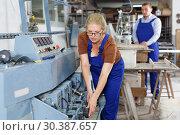Купить «Positive female working in workroom», фото № 30387657, снято 10 сентября 2018 г. (c) Яков Филимонов / Фотобанк Лори