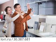 Купить «Couple looking at modern kitchen», фото № 30387681, снято 4 апреля 2017 г. (c) Яков Филимонов / Фотобанк Лори