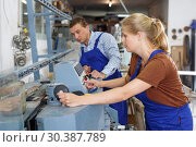 Купить «Female glazier with male colleague working on glass chamfering machine», фото № 30387789, снято 10 сентября 2018 г. (c) Яков Филимонов / Фотобанк Лори