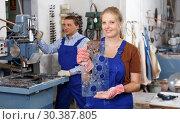 Купить «Female worker demonstrating drilled glass», фото № 30387805, снято 10 сентября 2018 г. (c) Яков Филимонов / Фотобанк Лори
