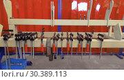 Купить «Clamps for fixing metal products. Clips hang on a metal beam», видеоролик № 30389113, снято 26 июля 2018 г. (c) Андрей Радченко / Фотобанк Лори