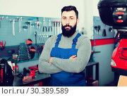Купить «bearded man worker displaying his workplace in motorcycle workshop», фото № 30389589, снято 19 июня 2019 г. (c) Яков Филимонов / Фотобанк Лори