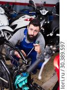 Купить «Worker repairing motorbike», фото № 30389597, снято 20 июня 2019 г. (c) Яков Филимонов / Фотобанк Лори