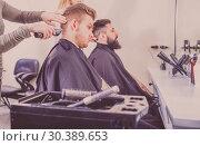 Купить «Young clients having their hair cut by hairdressers», фото № 30389653, снято 27 января 2017 г. (c) Яков Филимонов / Фотобанк Лори