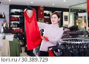Купить «Laughing customer deciding on pretty blouse», фото № 30389729, снято 7 февраля 2017 г. (c) Яков Филимонов / Фотобанк Лори