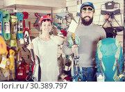 Купить «Couple choosing climbing equipment in sports shop», фото № 30389797, снято 24 февраля 2017 г. (c) Яков Филимонов / Фотобанк Лори