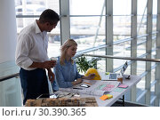 Купить «Caucasians architects interacting with each other at desk in office», фото № 30390365, снято 21 ноября 2018 г. (c) Wavebreak Media / Фотобанк Лори