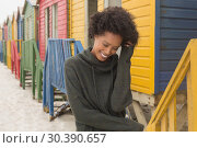 Купить «Young African American woman with hand in hair standing at beach hut», фото № 30390657, снято 14 ноября 2018 г. (c) Wavebreak Media / Фотобанк Лори