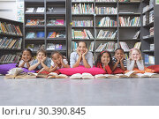 Купить «Happy schoolteacher and his school kids lying in a library », фото № 30390845, снято 17 ноября 2018 г. (c) Wavebreak Media / Фотобанк Лори