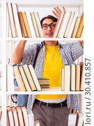 Купить «Male student preparing for exams at library», фото № 30410857, снято 14 декабря 2018 г. (c) Elnur / Фотобанк Лори