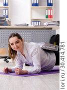Купить «Female employee doing sport exercises in the office», фото № 30414781, снято 6 ноября 2018 г. (c) Elnur / Фотобанк Лори