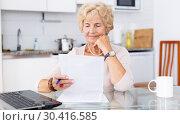 Купить «Mature woman filling up documents», фото № 30416585, снято 11 июля 2018 г. (c) Яков Филимонов / Фотобанк Лори
