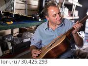 Купить «Man musician repairing instruments in workshop», фото № 30425293, снято 18 сентября 2017 г. (c) Яков Филимонов / Фотобанк Лори
