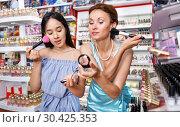 Купить «Girl and mother testing face powder at cosmetics shop», фото № 30425353, снято 21 июня 2018 г. (c) Яков Филимонов / Фотобанк Лори