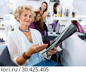 Купить «Smiling elderly female client sitting with magazine in chair in hair salon, choosing new hairstyle», фото № 30425405, снято 26 июня 2018 г. (c) Яков Филимонов / Фотобанк Лори