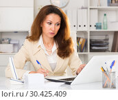 Купить «Young office woman is working with project behind laptop in the office.», фото № 30425409, снято 30 мая 2018 г. (c) Яков Филимонов / Фотобанк Лори