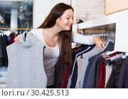 Купить «Positive adult woman buyer choosing sweater in shop», фото № 30425513, снято 17 января 2018 г. (c) Яков Филимонов / Фотобанк Лори