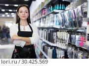 Купить «Woman hairstylist in apron standing in cosmetics studio», фото № 30425569, снято 31 марта 2018 г. (c) Яков Филимонов / Фотобанк Лори