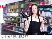 Купить «Woman hairstylist holding blow dryer and hair cutters in cosmetics salon», фото № 30425577, снято 31 марта 2018 г. (c) Яков Филимонов / Фотобанк Лори