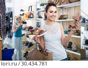 girl holding a picked pair of shoes in the boutique. Стоковое фото, фотограф Яков Филимонов / Фотобанк Лори
