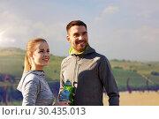 Купить «couple with bottles of water after sports outdoors», фото № 30435013, снято 17 октября 2015 г. (c) Syda Productions / Фотобанк Лори