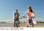 Купить «happy young couple riding bicycles at seaside», фото № 30435101, снято 23 июля 2017 г. (c) Syda Productions / Фотобанк Лори