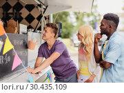 Купить «happy customers queue or friends at food truck», фото № 30435109, снято 1 августа 2017 г. (c) Syda Productions / Фотобанк Лори