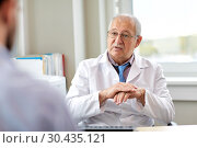 Купить «senior doctor talking to male patient at hospital», фото № 30435121, снято 6 октября 2017 г. (c) Syda Productions / Фотобанк Лори