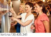 Купить «happy women pouring wine from dispenser at bar», фото № 30435341, снято 25 июня 2018 г. (c) Syda Productions / Фотобанк Лори